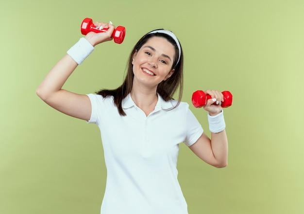 Mulher jovem fitness com uma faixa na cabeça, malhando com halteres, parecendo confiante sorrindo feliz e positiva em pé sobre a parede de luz