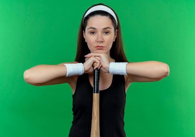Mulher jovem fitness com uma faixa na cabeça segurando o taco de basebal, olhando para a câmera com expressão confiante em pé sobre um fundo verde