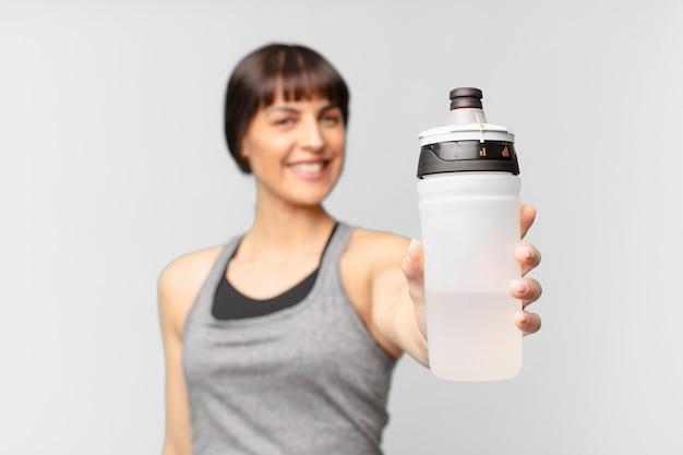 Mulher jovem fitness com uma lata de água
