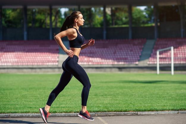 Mulher jovem fitness correndo em uma pista do estádio