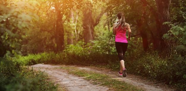 Mulher jovem fitness correndo na trilha da floresta de manhã. vida saudável e em forma.