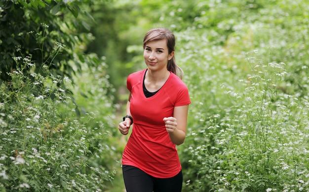 Mulher jovem fitness correndo na trilha da floresta de manhã.