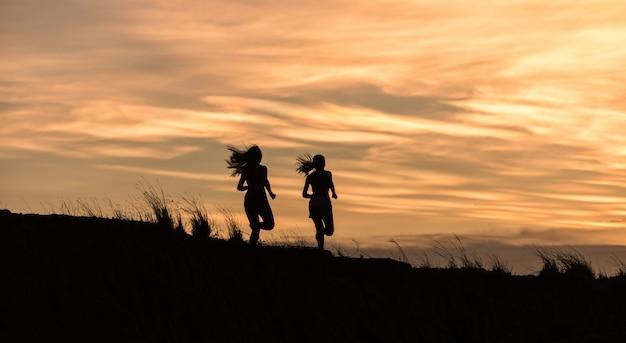 Mulher jovem fitness correndo no nascer do sol