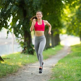 Mulher jovem fitness correndo no parque