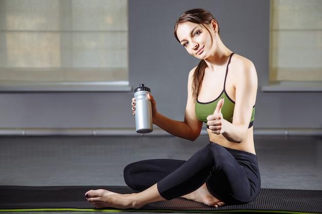 Mulher jovem fitness descansando depois de treino e mostra o polegar para cima