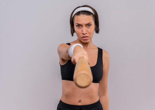 Mulher jovem fitness em roupas esportivas apontando com um taco de beisebol para a câmera com uma cara séria em pé sobre uma parede branca