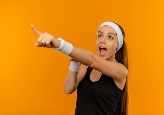 Mulher jovem fitness em roupas esportivas com bandana apontando com o dedo para algo surpreso em pé sobre a parede laranja
