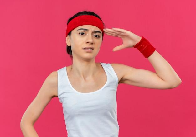 Mulher jovem fitness em roupas esportivas com bandana e expressão cética saudando em pé sobre a parede rosa