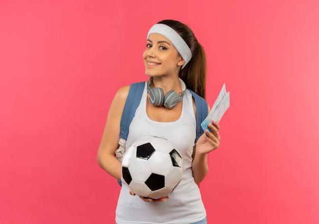 Mulher jovem fitness em roupas esportivas com bandana e fones de ouvido pendurados no pescoço segurando passagens aéreas e uma bola de futebol olhando para o lado com um sorriso no rosto em pé sobre a parede rosa