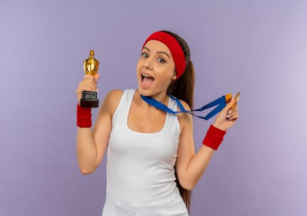 Mulher jovem fitness em roupas esportivas com bandana e medalha de ouro em volta do pescoço segurando seu troféu gritando feliz e animada em pé sobre a parede cinza
