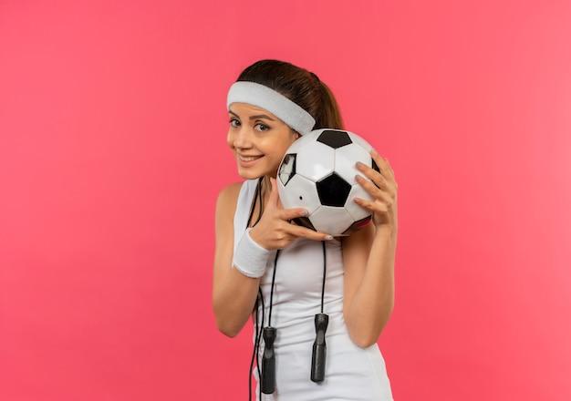 Mulher jovem fitness em roupas esportivas com bandana e pular corda no pescoço segurando uma bola de futebol com um sorriso no rosto em pé sobre a parede rosa