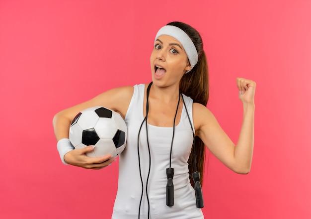 Mulher jovem fitness em roupas esportivas com bandana e pular corda no pescoço segurando uma bola de futebol parecendo surpresa