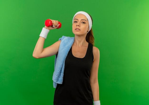 Mulher jovem fitness em roupas esportivas com bandana e toalha no ombro segurando halteres, fazendo exercícios, parecendo confiante em pé sobre a parede verde