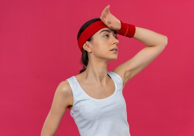 Mulher jovem fitness em roupas esportivas com bandana olhando para o lado com a mão na cabeça cansada após o treino em pé sobre a parede rosa