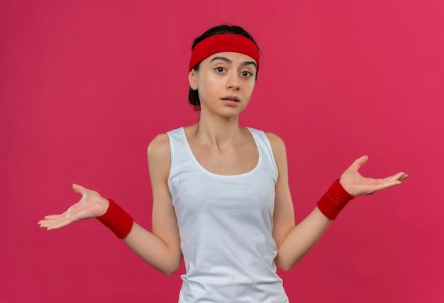 Mulher jovem fitness em roupas esportivas com bandana parecendo confusa e insegura, abrindo os braços para os lados sem resposta em pé sobre a parede rosa