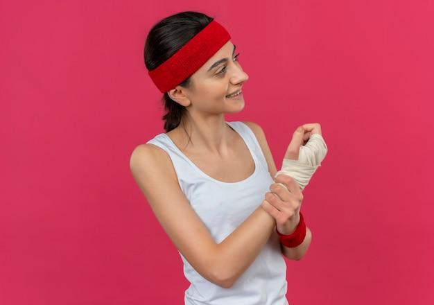 Mulher jovem fitness em roupas esportivas com bandana parecendo doente tocando seu pulso enfaixado sorrindo positivamente em pé sobre a parede rosa