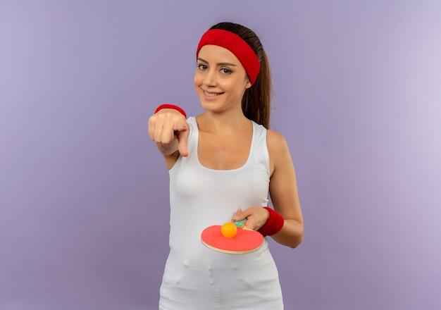 Mulher jovem fitness em roupas esportivas com bandana segurando a raquete e a bola de tênis de mesa apontando com o dedo indicador para a câmera com um sorriso no rosto em pé sobre a parede cinza