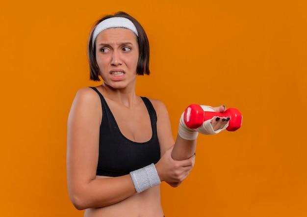 Mulher jovem fitness em roupas esportivas com bandana segurando halteres tocando seu pulso, parecendo doente, sofrendo de dor em pé sobre a parede laranja