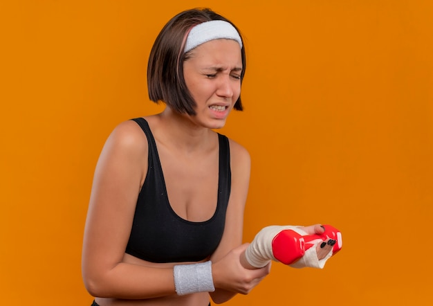 Mulher jovem fitness em roupas esportivas com bandana segurando halteres tocando seu pulso, parecendo indisposta, sentindo dor em pé sobre a parede laranja