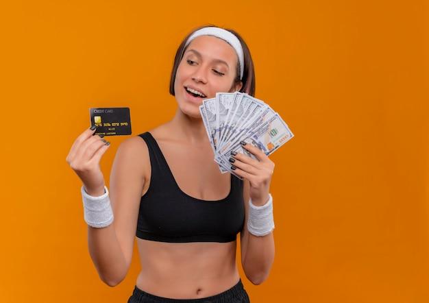 Mulher jovem fitness em roupas esportivas com bandana segurando um cartão de crédito e mostrando dinheiro sorrindo alegremente em pé sobre a parede laranja