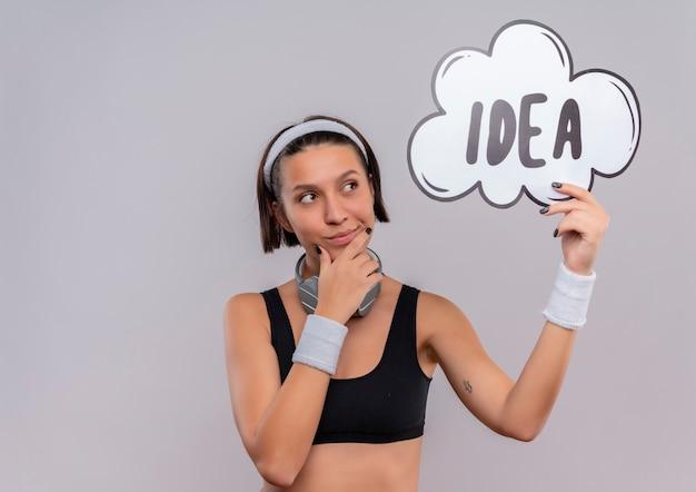 Mulher jovem fitness em roupas esportivas com bandana segurando um cartaz de bolha do discurso com a ideia da palavra olhando para o lado com expressão pensativa em pé sobre uma parede branca