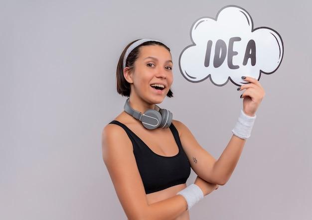 Mulher jovem fitness em roupas esportivas com bandana segurando um cartaz de bolha do discurso com a palavra ideia feliz e positiva sorrindo alegremente em pé sobre uma parede branca