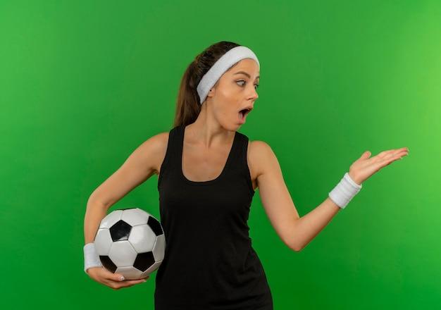 Mulher jovem fitness em roupas esportivas com bandana segurando uma bola de futebol apontando com o braço da mão para o lado, parecendo surpresa em pé sobre a parede verde