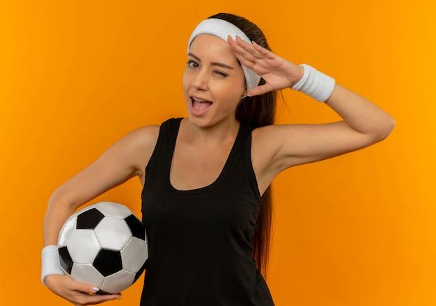 Mulher jovem fitness em roupas esportivas com bandana segurando uma bola de futebol, piscando e sorrindo, saudando em pé sobre a parede laranja