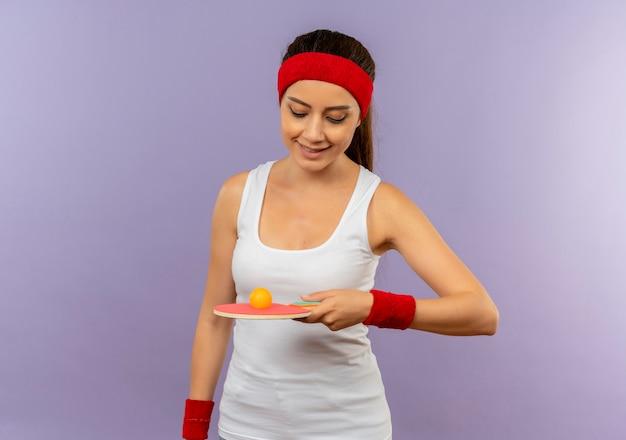 Mulher jovem fitness em roupas esportivas com bandana segurando uma raquete e uma bola de tênis de mesa olhando para ela com um sorriso no rosto em pé sobre a parede cinza