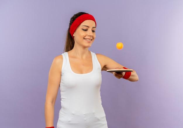 Mulher jovem fitness em roupas esportivas com bandana segurando uma raquete e uma bola de tênis de mesa sorrindo alegremente em pé sobre uma parede cinza