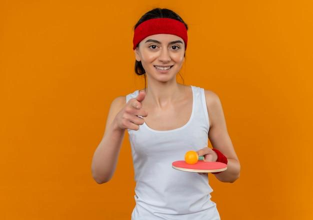 Mulher jovem fitness em roupas esportivas com bandana segurando uma raquete e uma bola de tênis de mesa sorrindo com uma cara feliz