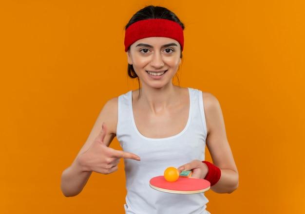Mulher jovem fitness em roupas esportivas com bandana segurando uma raquete e uma bola de tênis de mesa