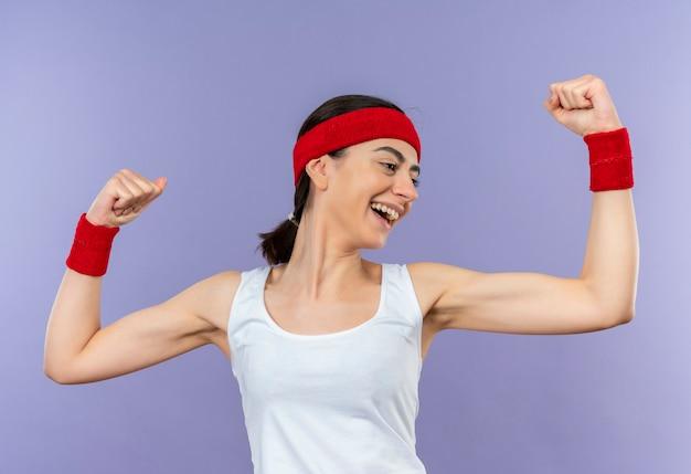 Mulher jovem fitness em roupas esportivas com bandana sorrindo alegremente levantando os punhos feliz e positiva em pé sobre a parede roxa