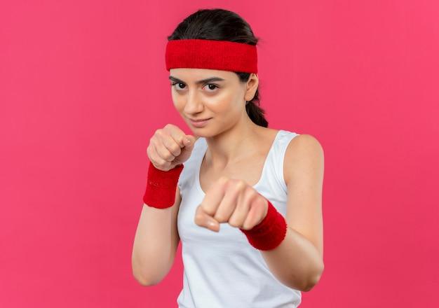 Mulher jovem fitness em roupas esportivas com bandana sorrindo, posando como um boxeador com os punhos em pé sobre a parede rosa