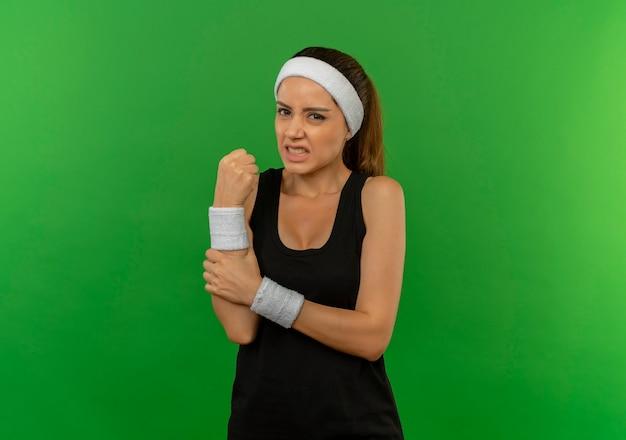 Mulher jovem fitness em roupas esportivas com bandana tocando seu pulso, sentindo dor em pé sobre a parede verde