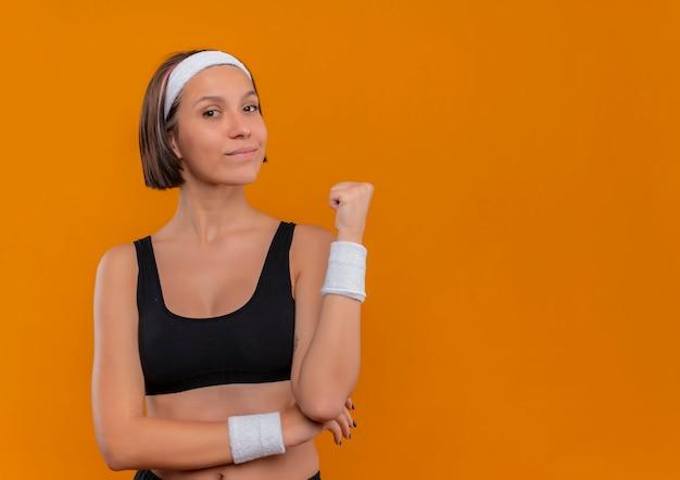 Mulher jovem fitness em roupas esportivas com fita para a cabeça, apontando para trás, parecendo confiante em pé sobre a parede laranja