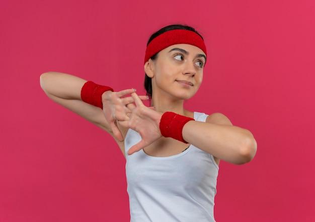 Mulher jovem fitness em roupas esportivas com fita para a cabeça, olhando para o lado, aquecendo em pé sobre a parede rosa
