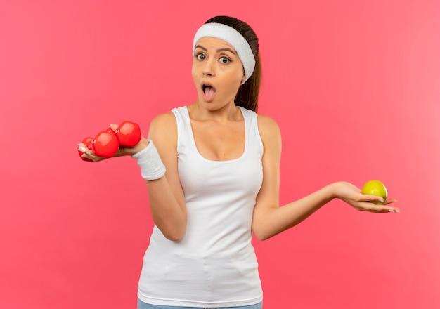 Mulher jovem fitness em roupas esportivas com fita para a cabeça segurando dois halteres e uma maçã verde, parecendo surpresa e espantada em pé sobre a parede rosa