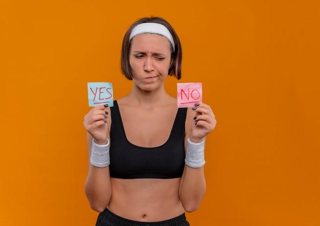Mulher jovem fitness em roupas esportivas com fita para a cabeça segurando dois papéis-lembrete com a palavra sim e não nas mãos levantadas, olhando para eles com expressão cética em pé sobre a parede laranja