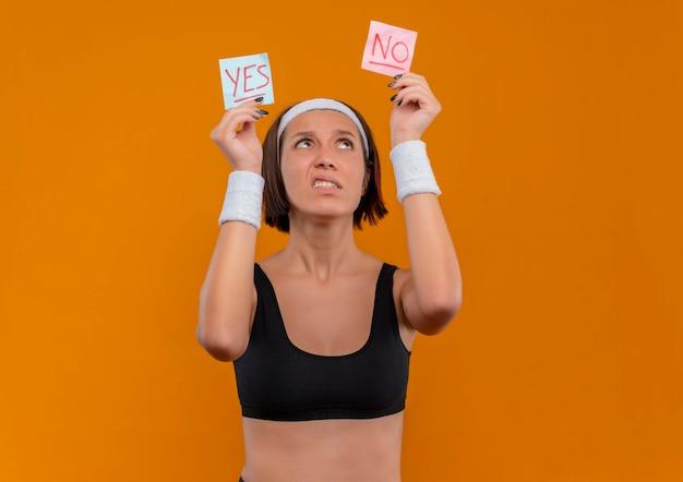 Mulher jovem fitness em roupas esportivas com fita para a cabeça segurando dois papéis-lembrete com a palavra sim e não nas mãos levantadas olhando para eles confusa em pé sobre a parede laranja