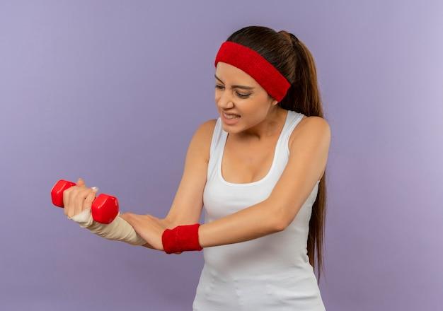 Mulher jovem fitness em roupas esportivas com fita para a cabeça, segurando halteres, tocando seu braço enfaixado, parecendo indisposta em pé sobre uma parede cinza