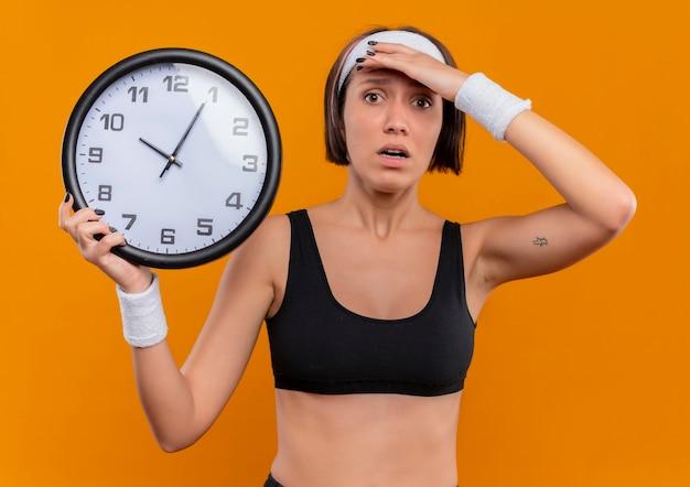 Mulher jovem fitness em roupas esportivas com fita para a cabeça, segurando o relógio de parede com a mão na cabeça, parecendo confusa e muito ansiosa em pé sobre a parede laranja