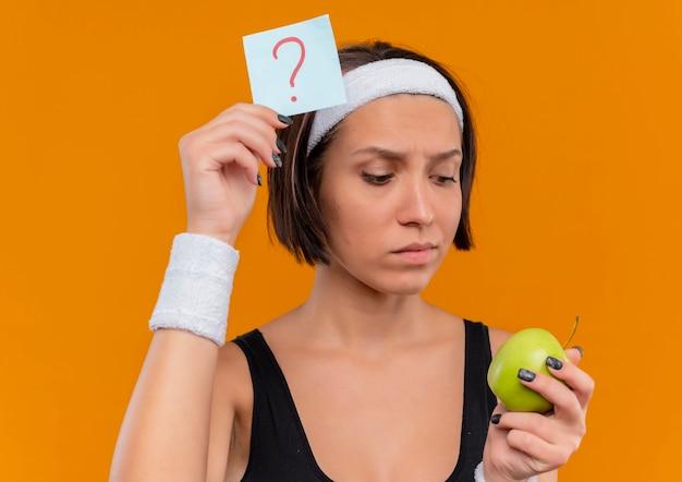Mulher jovem fitness em roupas esportivas com fita para a cabeça segurando papel lembrete com ponto de interrogação e maçã verde olhando para uma maçã com expressão pensativa em pé sobre a parede laranja