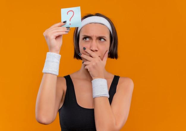 Mulher jovem fitness em roupas esportivas com fita para a cabeça segurando papel lembrete com ponto de interrogação olhando para ele com expressão pensativa pensando em pé sobre a parede laranja