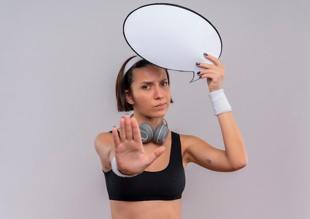 Mulher jovem fitness em roupas esportivas com fita para a cabeça, segurando um cartaz de bolha de discurso em branco, fazendo sinal de pare com a mão com uma cara séria em pé sobre uma parede branca