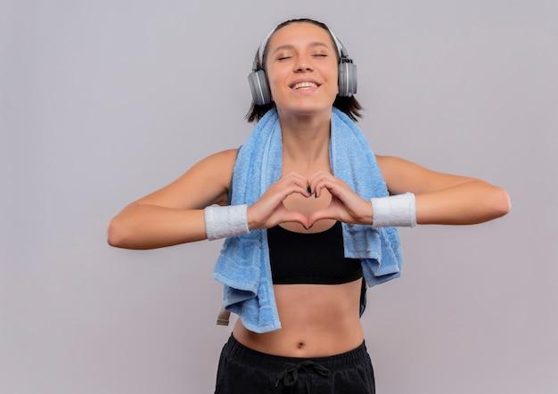 Mulher jovem fitness em roupas esportivas com fones de ouvido na cabeça e toalha no pescoço fazendo um gesto de coração com os dedos com os olhos fechados, sentindo emoções positivas em pé sobre uma parede branca