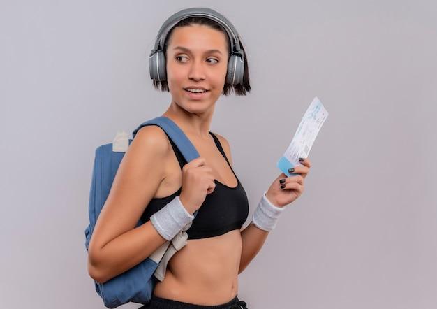 Mulher jovem fitness em roupas esportivas com fones de ouvido na cabeça segurando a passagem aérea olhando para o lado com um sorriso no rosto em pé sobre uma parede branca