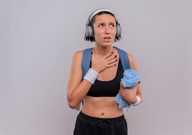 Mulher jovem fitness em roupas esportivas com mochila e fones de ouvido na cabeça, segurando uma toalha com a mão no peito, olhando de lado preocupada em pé sobre uma parede branca