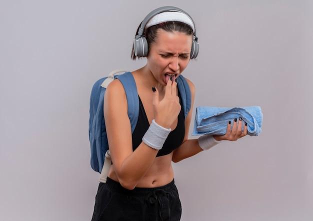 Mulher jovem fitness em roupas esportivas com mochila e fones de ouvido na cabeça segurando uma toalha e mostrando a língua com expressão de nojo em pé sobre uma parede branca