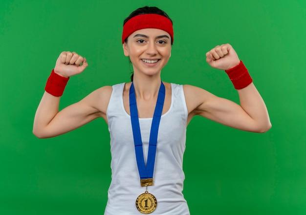 Mulher jovem fitness em roupas esportivas com tiara e medalha de ouro no pescoço levantando os punhos como uma vencedora sorrindo confiante em pé sobre a parede verde